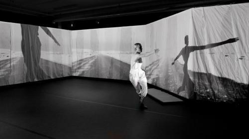 Helena Franzén dansar på scen omringad av stora projektioner av natur.