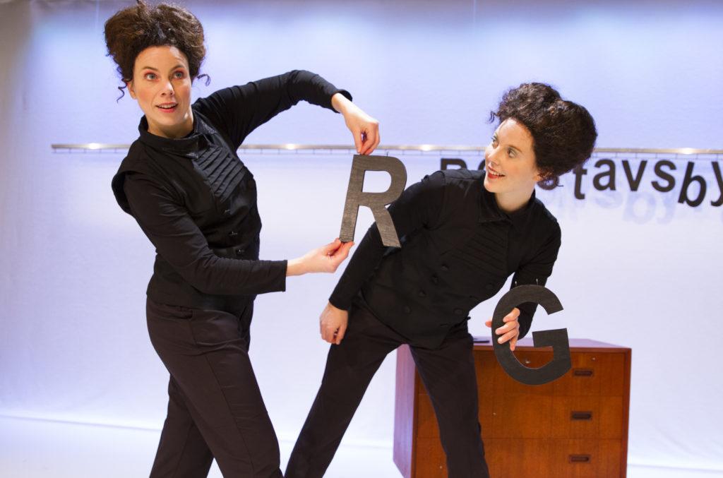 Två kvinnliga dansare håller upp bokstäver.