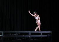 En kvinnlig dansare i ett mörkt scenrum, sträcker ut sin arm.