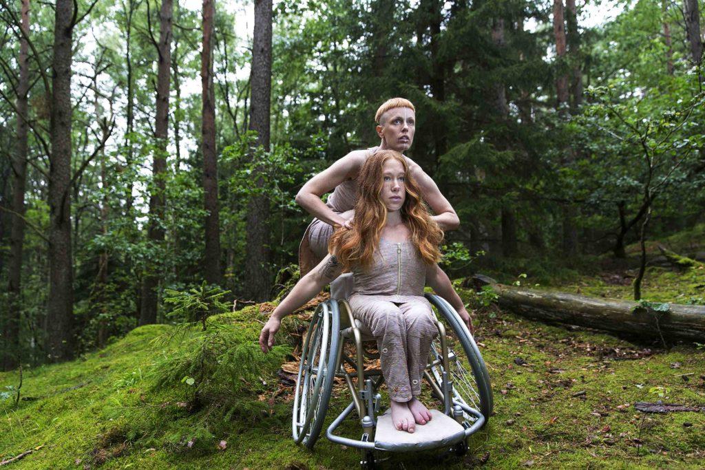 Två dansare i skogen. Den ena i rullstol den andra står bakom.